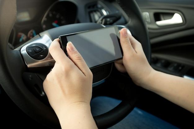 Foto en primer plano del conductor escribiendo un mensaje mientras conduce un automóvil