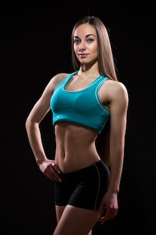 Foto en primer plano de un cuerpo de modelo de fitness sobre fondo negro