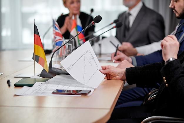 Foto de primer plano del documento gráfico en manos de la ejecutiva durante la reunión de negocios interracial en la oficina moderna, gente sentada en el escritorio