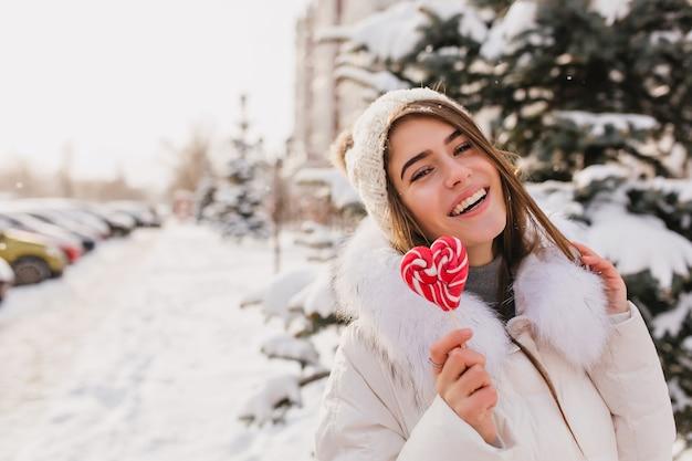Foto de primer plano de encantadora mujer de pelo largo caminando por la calle nevada con piruleta. mujer bonita riendo con gorro de punto disfrutando de fin de semana de invierno al aire libre.