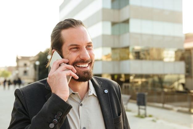 Foto de primer plano de exitoso hombre corporativo o gerente de oficina en traje sonriendo, mientras está de pie frente al centro de negocios y hablando por teléfono inteligente