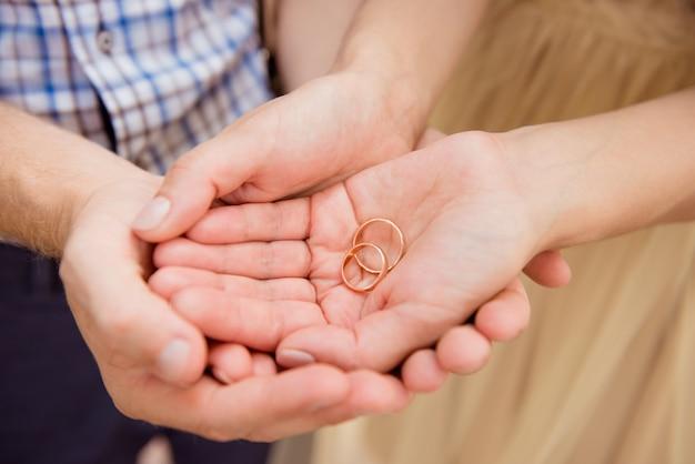 Foto en primer plano de una feliz pareja de enamorados sosteniendo anillos de boda