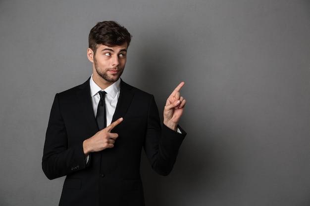 Foto de primer plano de guapo hombre morena en traje negro apuntando con dos dedos hacia arriba