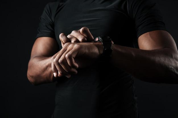 Foto de primer plano del hombre africano en camiseta negra, echa un vistazo a la hora en el reloj de pulsera negro