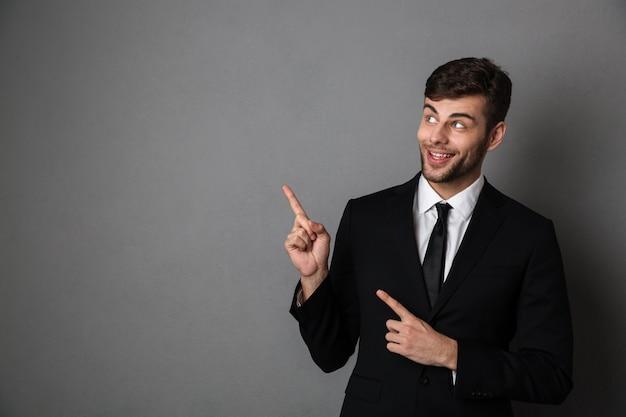 Foto de primer plano de hombre guapo con barba en traje negro poiting con dos dedos, mirando a un lado