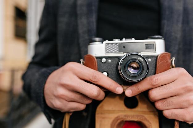 Foto de primer plano de hombre con piel morena de pie en la calle después de la sesión de fotos. retrato al aire libre de manos masculinas sosteniendo la cámara.