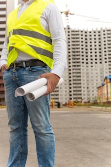 Foto en primer plano del ingeniero de la construcción de pie en el sitio de construcción y sosteniendo planos