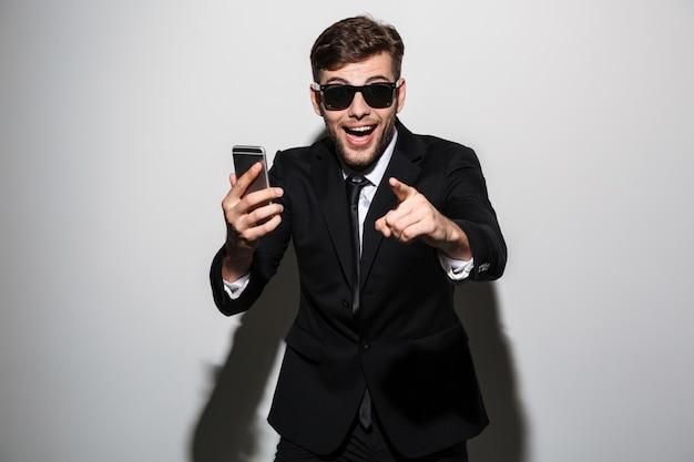 Foto de primer plano del joven hombre feliz feliz salido en gafas de sol con smartphone y apuntando con el dedo