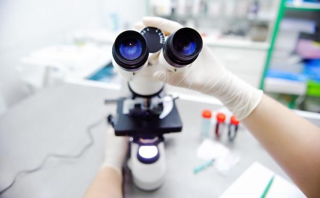 Foto de primer plano de manos del científico con microscopio, examinando sam