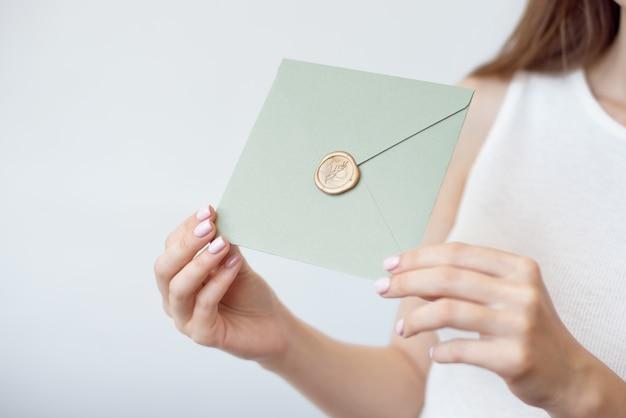 Foto de primer plano de manos femeninas con sobre de invitación con un sello de cera dorada, certificado de regalo, postal, tarjeta de invitación de boda