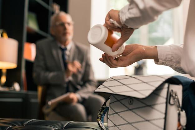 Foto en primer plano de las manos de los pacientes tomando pastillas de un pastillero en la oficina de los psicoterapeutas