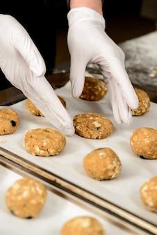 Foto de primer plano de manos poniendo sabrosas galletas en una bandeja para hornear