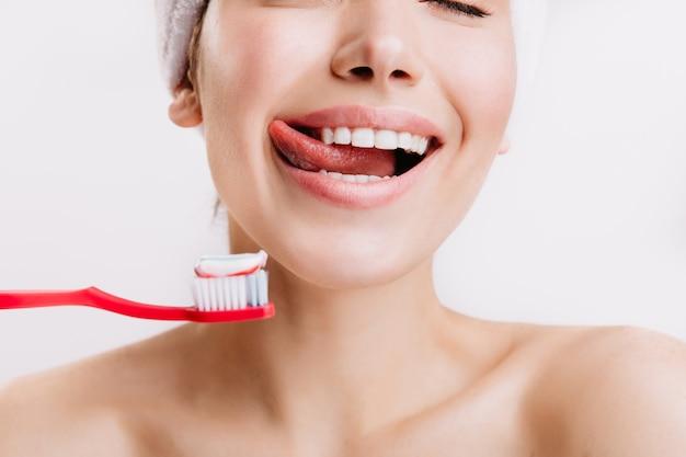 Foto de primer plano de mujer anticipando el cepillado de dientes. modelo con sonrisa blanca como la nieve posando en la pared blanca.