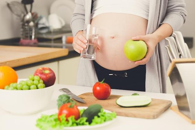 Foto en primer plano de la mujer embarazada posando en la cocina con manzana y vaso de agua