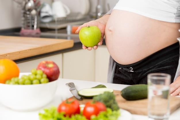 Foto en primer plano de la mujer embarazada posando con manzana verde en la cocina