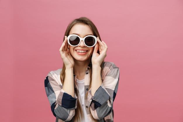 Foto de primer plano de una mujer encantadora con un largo peinado con gafas de sol de moda