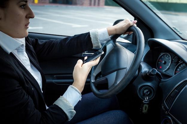 Foto en primer plano de una mujer joven conduciendo un coche y escribiendo un mensaje