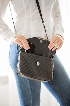 Foto en primer plano de una mujer joven y elegante sacando el teléfono móvil del bolso