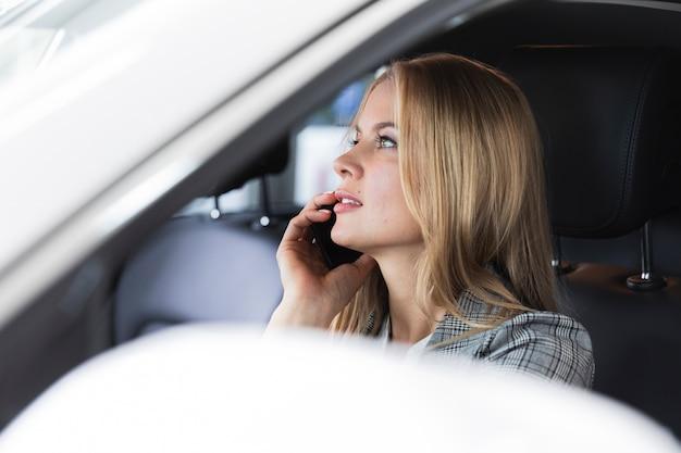 Foto de primer plano de una mujer rubia hablando por teléfono