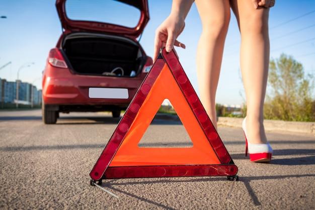 Foto de primer plano de mujer sexy poniendo señal de advertencia en la carretera