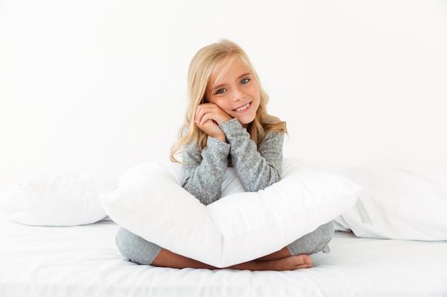 Foto de primer plano de niña bonita rubia sentada con las piernas cruzadas en la cama blanca, sosteniendo su cabeza,