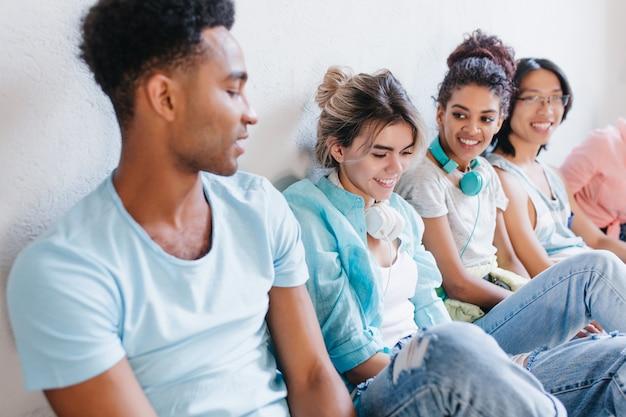 Foto de primer plano de niño africano con camisa azul mirando chicas guapas lleva pantalones de mezclilla. retrato interior de estudiantes hablando de sus estudios con interés.