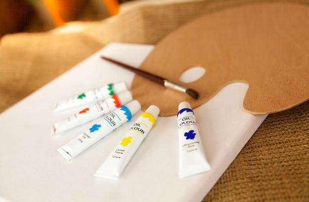 Foto en primer plano de la paleta y los tubos de pintura al óleo sobre lienzo blanco