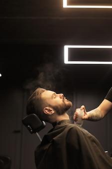 Foto de primer plano de un peluquero profesional, que arregla la barba de su joven cliente, que se mira en el espejo durante el procedimiento.