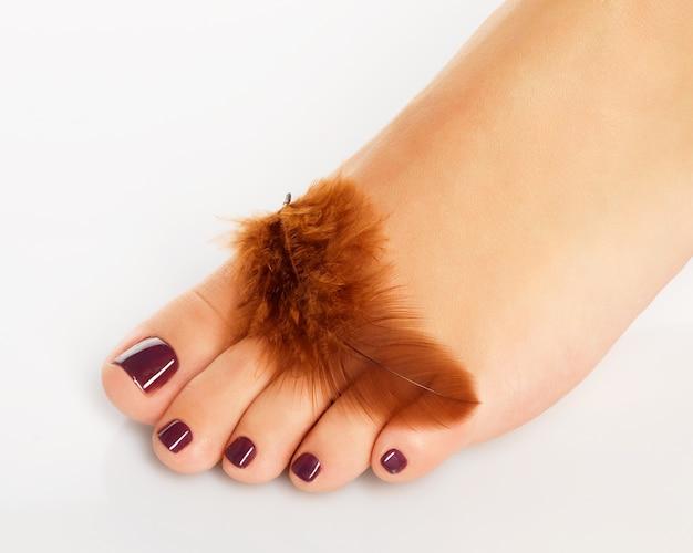 Foto de primer plano de un pie femenino con hermosa pedicura después del procedimiento de spa en blanco