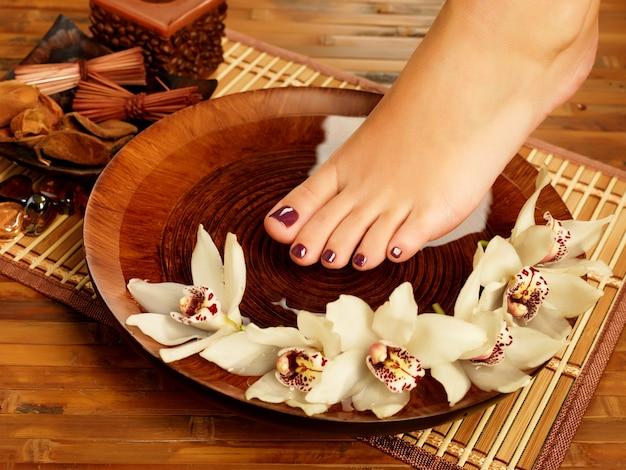 Foto de primer plano de un pie femenino en el salón de spa en el procedimiento de pedicura - imagen de enfoque suave