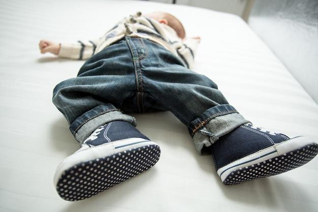 Foto en primer plano de los pies del bebé en jeans y zapatillas de deporte acostado en la cama