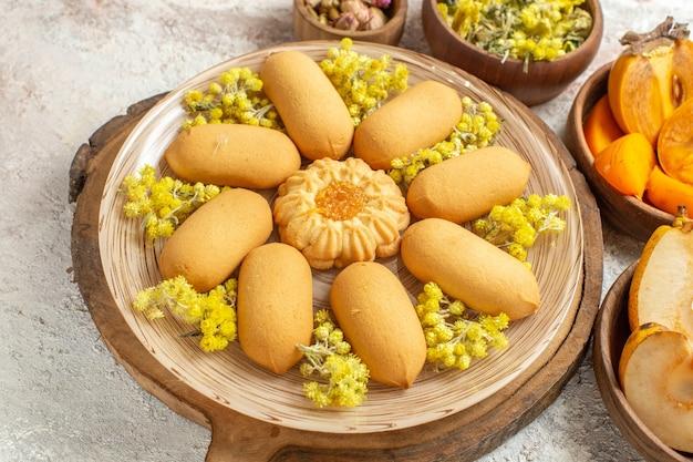 Foto de primer plano de un plato de galletas dulces en un plato de madera y diferentes ingredientes a su alrededor