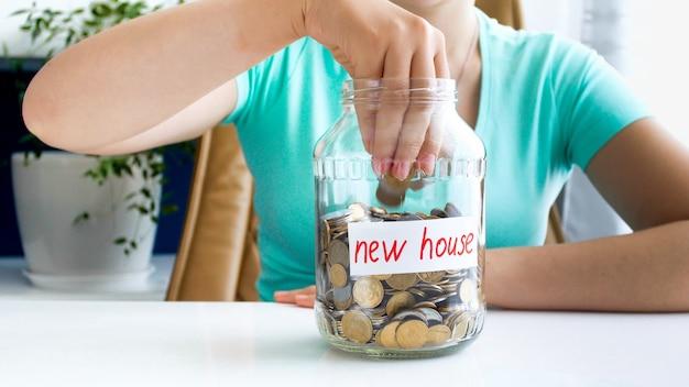 Foto de primer plano de la señorita en camiseta azul sentada en la mesa blanca en la que se encuentra, llena de monedas, tarro con la inscripción nueva casa.