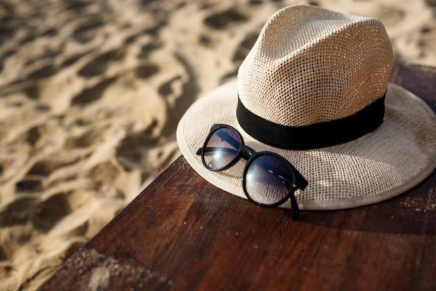 Foto de primer plano de sombrero y gafas en la playa