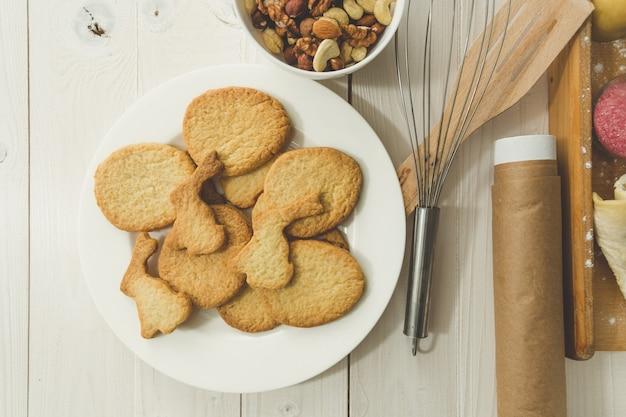 Foto en primer plano de tonos de cocinar recién horneados junto a los utensilios de cocina en la mesa de madera blanca