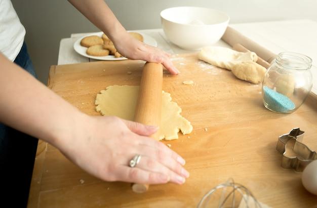 Foto en primer plano de tonos de mujer haciendo masa para galletas sobre tabla de madera