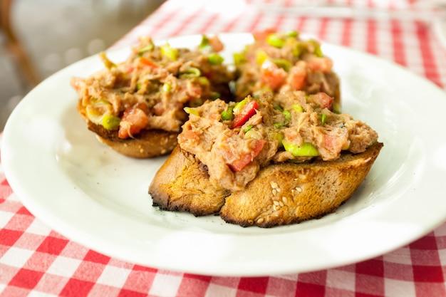 Foto en primer plano de tres bruschettas con atún en un plato en el restaurante