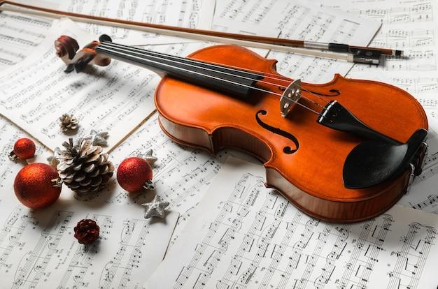 Foto de primer plano de violín, notas musicales y decoración navideña