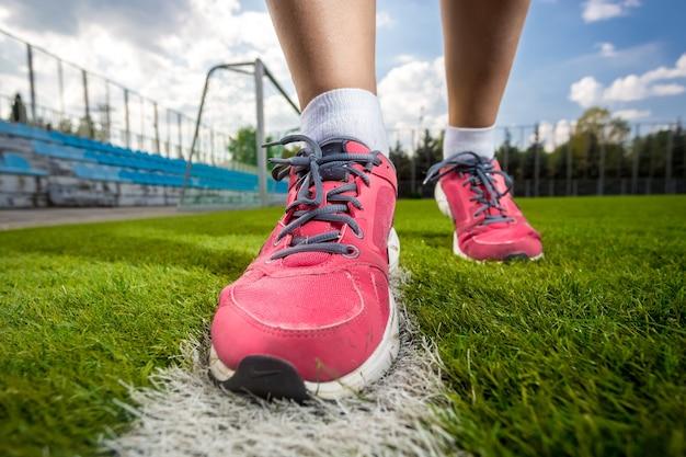 Foto en primer plano de zapatillas de deporte femeninas rosas en el campo de hierba de fútbol