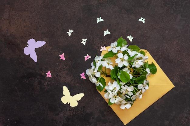 La foto del primer de las ramas florecientes blancas de cherry tree en sobre del oro con las pequeñas estatuillas de la mariposa. vista superior, tarjeta de greating.