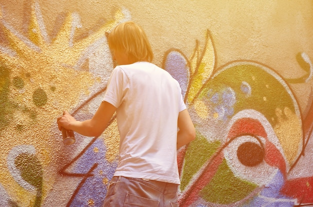 Foto en proceso de dibujar un patrón de graffiti en un viejo muro de concreto