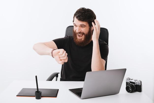 Foto de un profesional independiente con barba preocupada, estresado por el tiempo restante, antes de la fecha límite