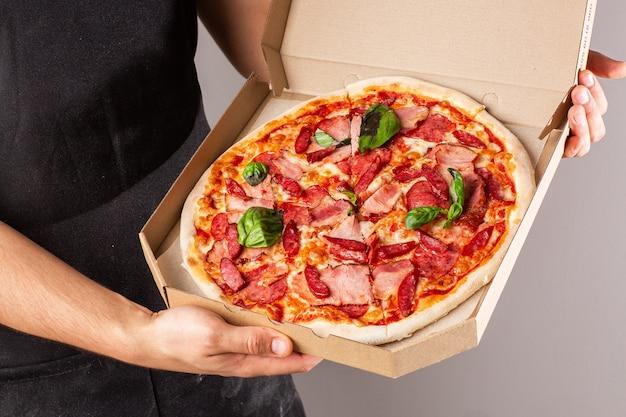 Foto publicitaria de un sitio o menú. pizza con jamón y salami en una caja en las manos de un joven en delantal oscuro. fondo brillante.