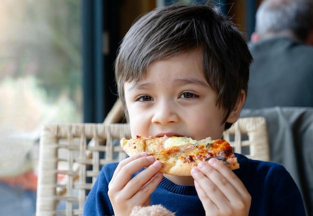 Foto recortada chico lindo niño comiendo pizza casera en el café