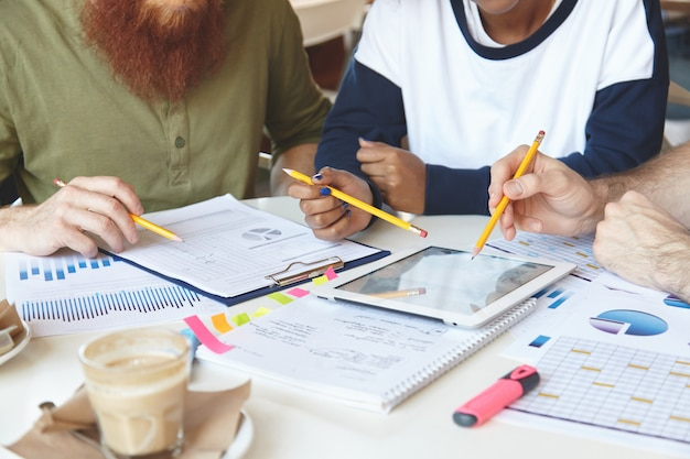 Foto recortada de compañeros de trabajo trabajando juntos y analizando cifras financieras en gráficos y diagramas.