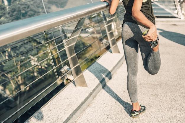 Foto recortada de una deportista en mallas y zapatillas de deporte poniendo el pie hacia atrás durante el calentamiento.
