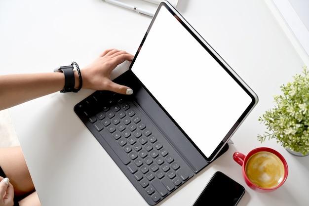 Foto recortada del diseñador creativo que trabaja con una tableta y un teclado modernos en una mesa blanca en el espacio de trabajo del estudio