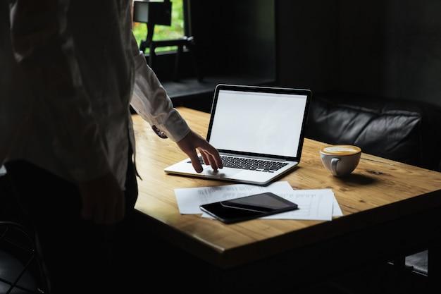 Foto recortada del empresario en camisa blanca de pie cerca de la mesa de madera, escribiendo en la computadora portátil