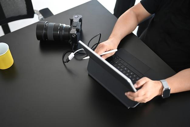 Foto recortada de fotógrafo masculino está retocando fotos con tableta de computadora en su espacio de trabajo creativo.