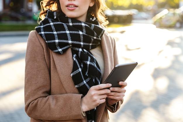 Foto recortada de una hermosa joven al aire libre caminando por la calle con tablet pc.